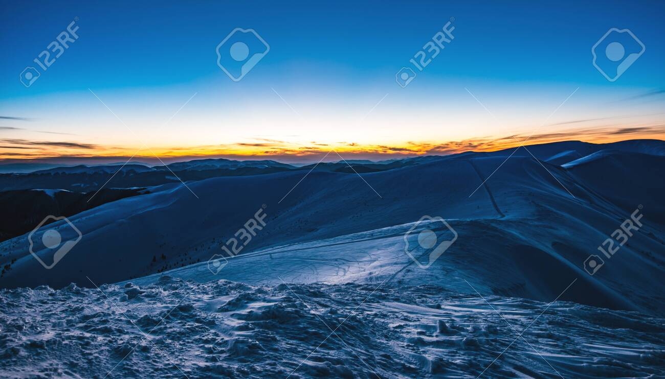 Stunning beautiful views of the slopes in the ski resort after sunset in the late evening. The concept of vacation in the northern country on holidays and New Year holidays - 133873667