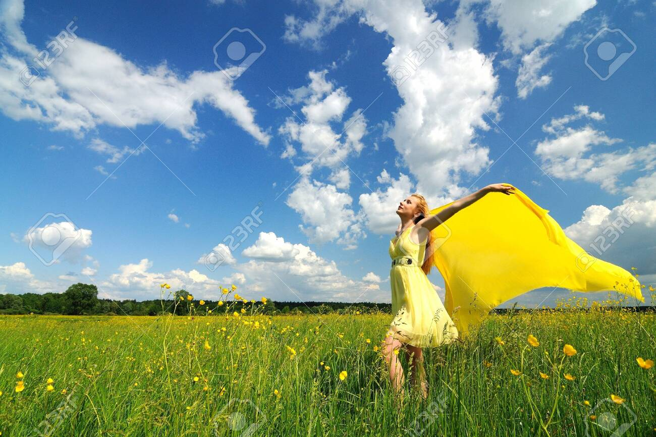 A girl in a yellow dress poses with hands up in a green field with a silk cloth in her hands. Beautiful outdoor photo - 138897438