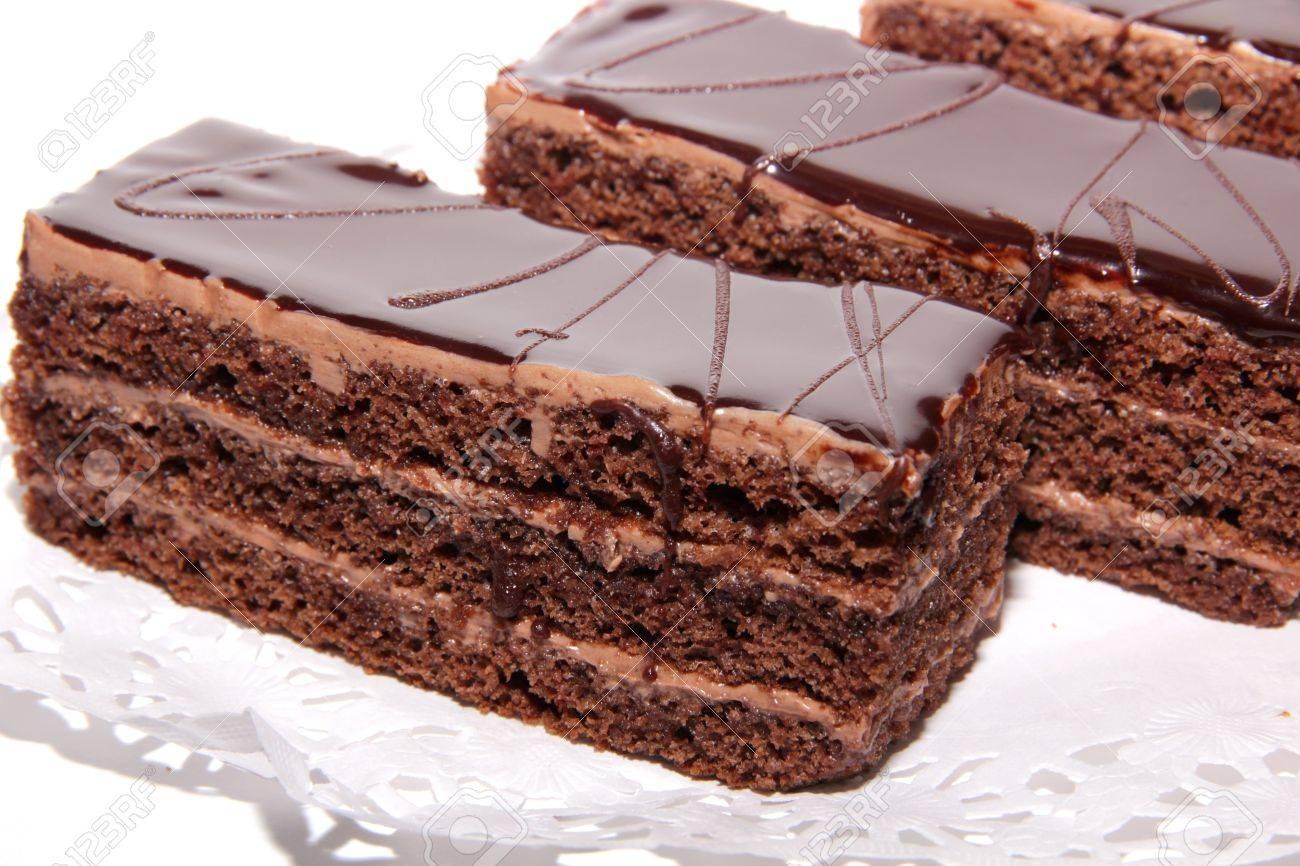 Three chocolate cake with cream and chocolate glaze on a lace napkin Stock Photo - 12221216