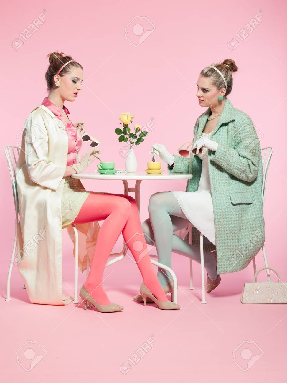 Two girls blonde hair fifties fashion style drinking tea Stock Photo - 18190144