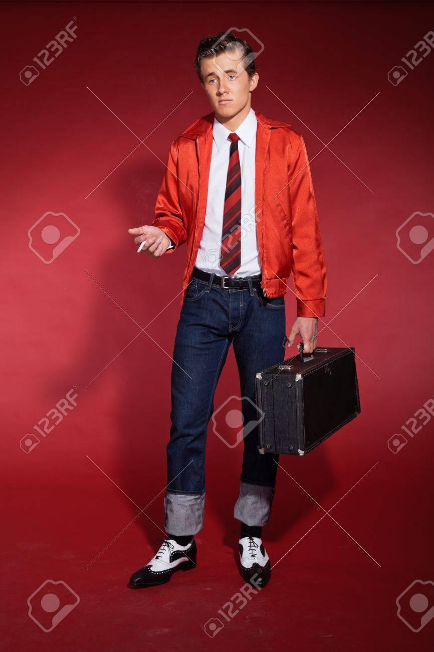 new product 0f4b4 aec17 Retrò anni Cinquanta moda uomo che indossa giacca rossa e jeans. In  possesso di un caso e di fumare.