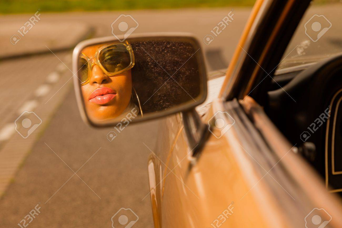 Retro 70s afro fashion woman with sunglasses looking in mirror of brown seventies car. Stock Photo - 20281149