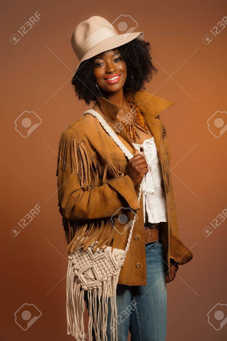 retro 70er jahre mode afrikanische frau mit weissem hut und braune jacke brown hintergrund
