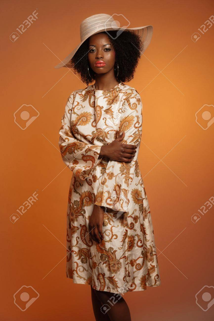 retro 70er jahre mode afrofrau mit paisley kleid und weissem hut brown hintergrund