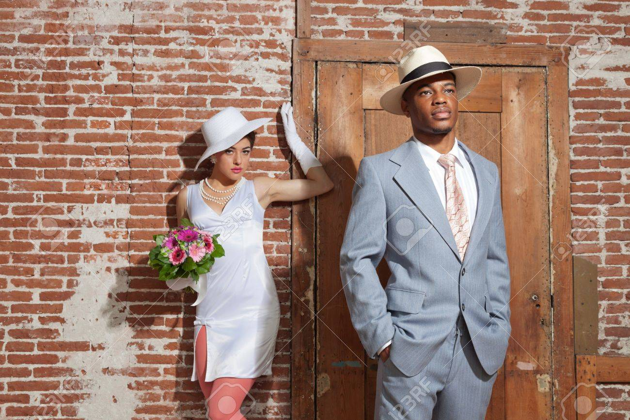 Wearing a hat. Retro jazz fashion wedding couple in old urban building.  Groom in focus. Mixed race 21f4a8e6c82