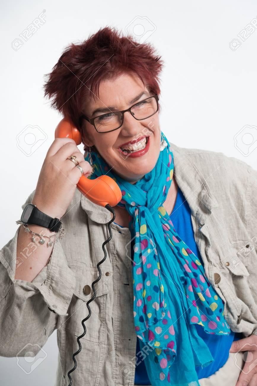 Archivio Fotografico - Donna di mezza età che chiama con il telefono  arancione vintage. Rossa dei capelli corti e gli occhiali. Studio shot. f9dc83dcc060