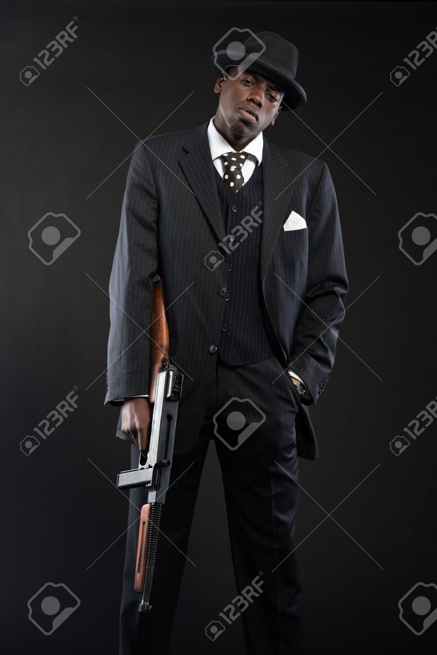 Retro african american mafia man wearing striped suit and tie and black hat.  Holding machine 2f2c41c3d4ae
