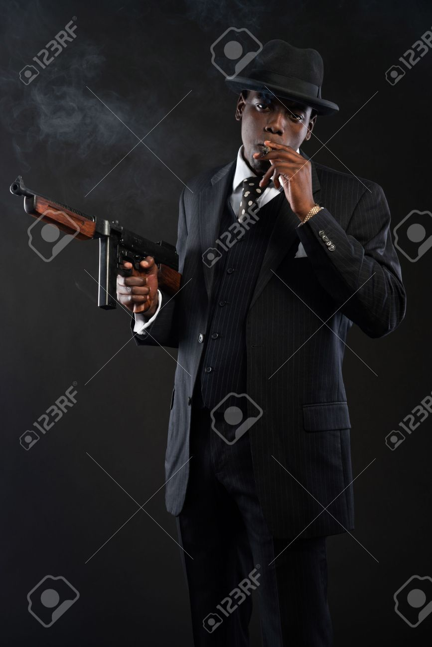 Retro african american mafia man wearing striped suit and tie and black hat.  Smoking cigar 2b10e99e6715