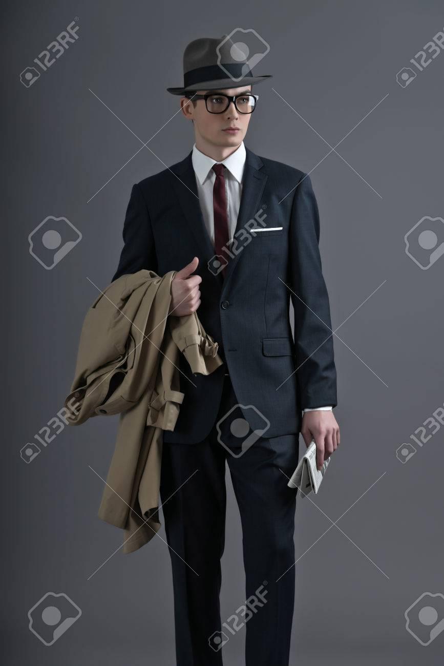Archivio Fotografico - Retrò anni Cinquanta moda giovane uomo con gli  occhiali e il cappello che indossa abito scuro. In possesso di un  impermeabile e ... 69527831a490