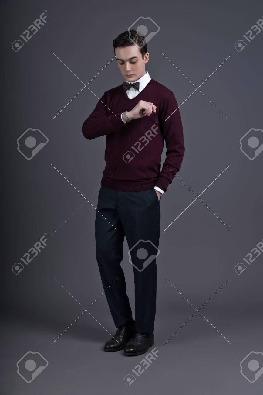 official photos 923fa ae9ce Cinquanta retrò stile inglese di moda uomo guardando l'orologio. Indossa la  camicia rosso scuro e farfallino. Studio sparato contro grigio.