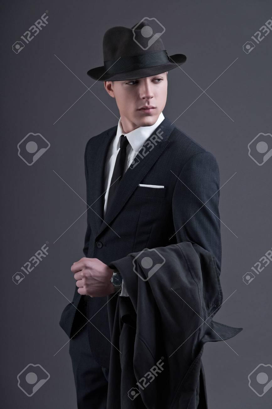 Archivio Fotografico - Retrò anni Cinquanta moda giovane uomo d affari con  il cappello che indossa abito scuro e cravatta. In possesso di un  impermeabile. 9830992d6452
