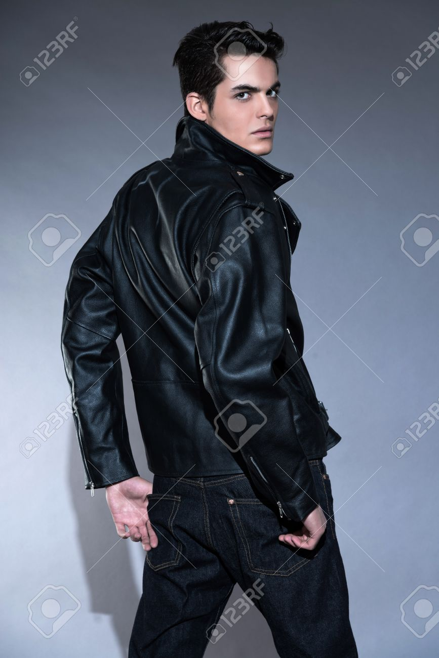 Retro rock and roll 50s fashion man with dark grease hair. Wearing black leather jacket and jeans. Studio shot against grey