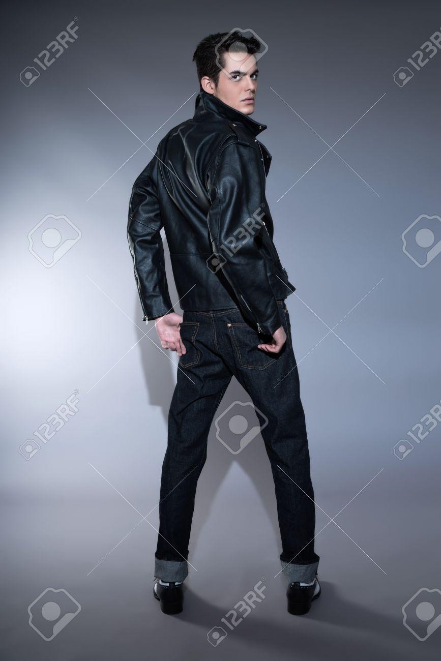 El Hombre De Moda Retro Anos 50 El Rock Y Rollo Con El Pelo Oscuro Grasa El Uso De La Chaqueta De Cuero Negro Y Pantalones Vaqueros Foto De Estudio Sobre Gris