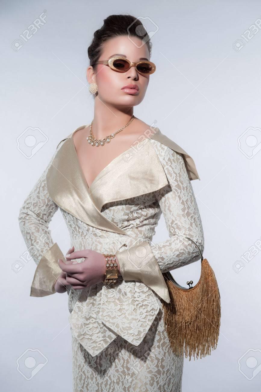 Banque d images - Glamour années 50 la mode rétro femme avec des lunettes  tenant un sac à main d or. Portant robe légère. Studio photo sur gris. da7ebc1906f1