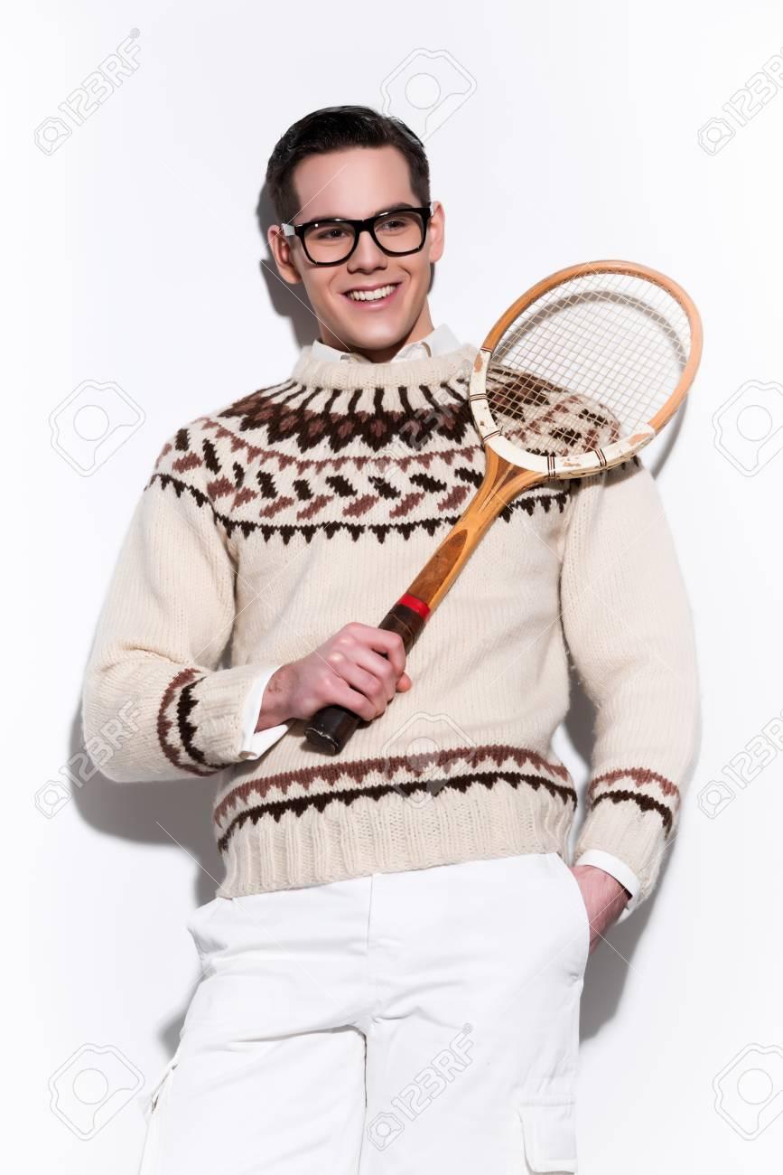 Rétro homme de mode de tennis avec des lunettes de soleil tenant une raquette en bois vintage. Studio shot sur blanc.