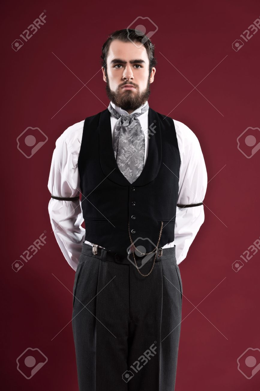 Banque d\u0027images , Retro homme 1900 de la mode victorienne avec une barbe  portant gilet noir et cravate grise. Tourné en studio contre le mur rouge.