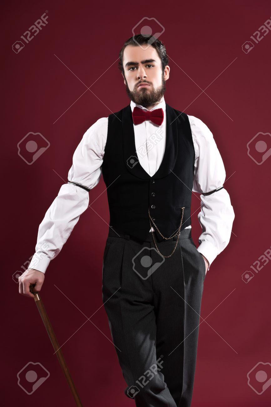 vente limitée comment trouver photos officielles Rétro 1900 victorienne homme de mode avec la barbe portant gilet noir et  rouge noeud papillon. Tenant un bâton de marche. Studio abattu contre le  mur ...