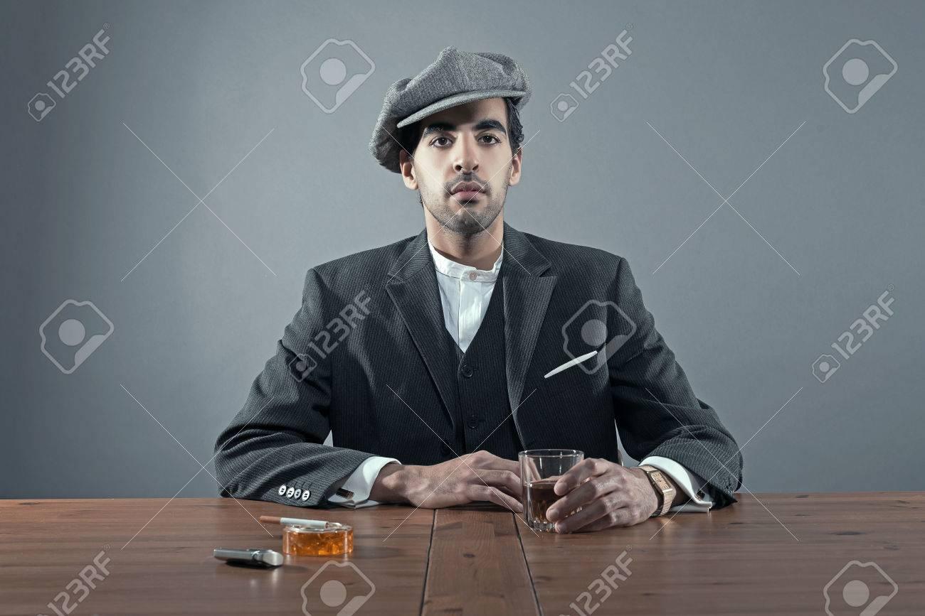 マフィア ファッション男キャップ グレー ストライプ スーツを着ています。ウイスキーやタバコの