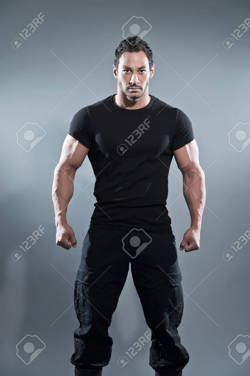 41992e90a4 Combat muscled fitness man wearing black shirt and pants. Studio shot  against grey. Stock