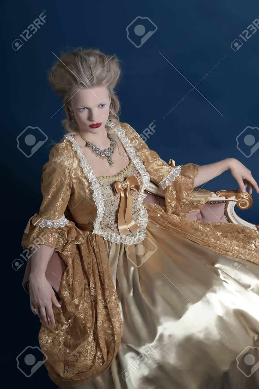 La En Sofá Barroco Mujer Moda VendimiaFoto Vestido Un Azul Con El De Estudio Sobre Retro OroSentado n8kwOP0