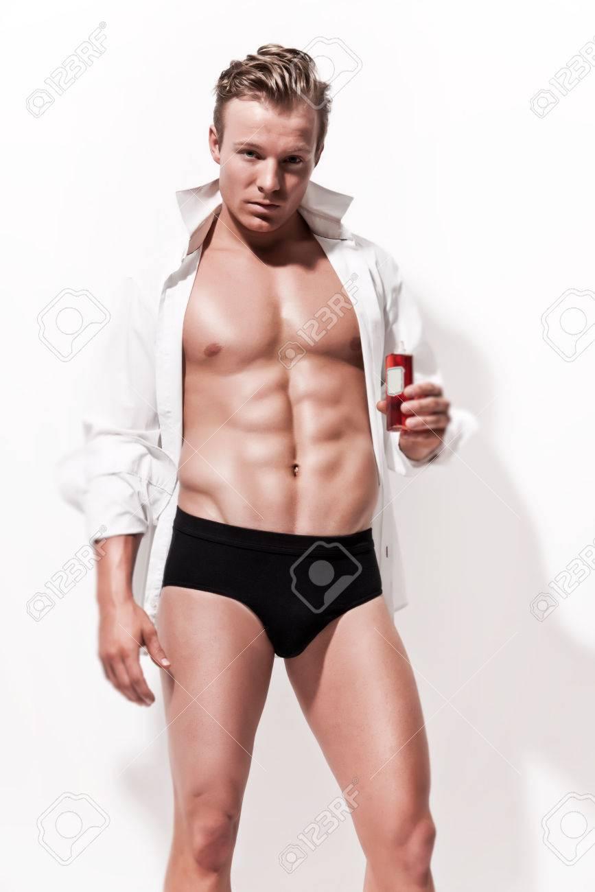 3589d2073b6c Modelo de ropa interior masculina musculoso vistiendo la camiseta blanca.  La celebración de botella de la vendimia de la grasa. Pelo rubio. Contra la  ...