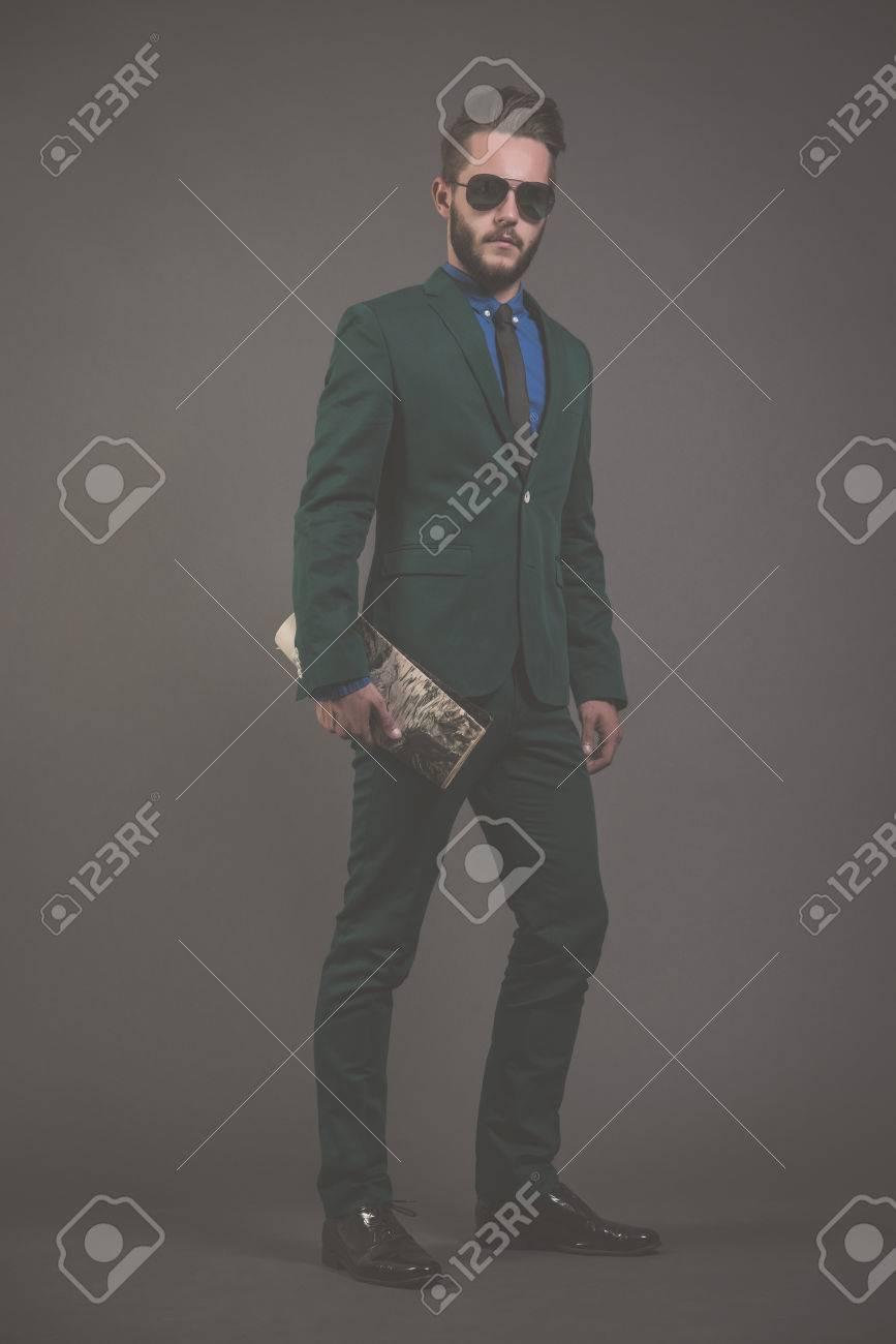 cd7ed92a322578 Business-Mode Mann mit grünen Anzug mit Sonnenbrille und blauem Hemd und  schwarzer Krawatte.