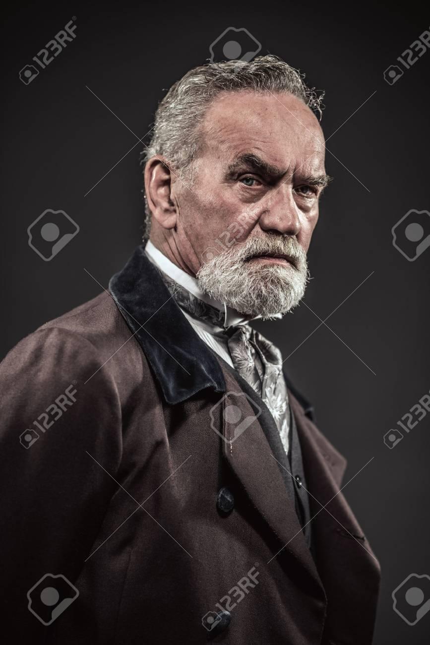 Vintage characteristic senior man with gray hair and beard. Studio shot against dark background. Stock Photo - 32035027