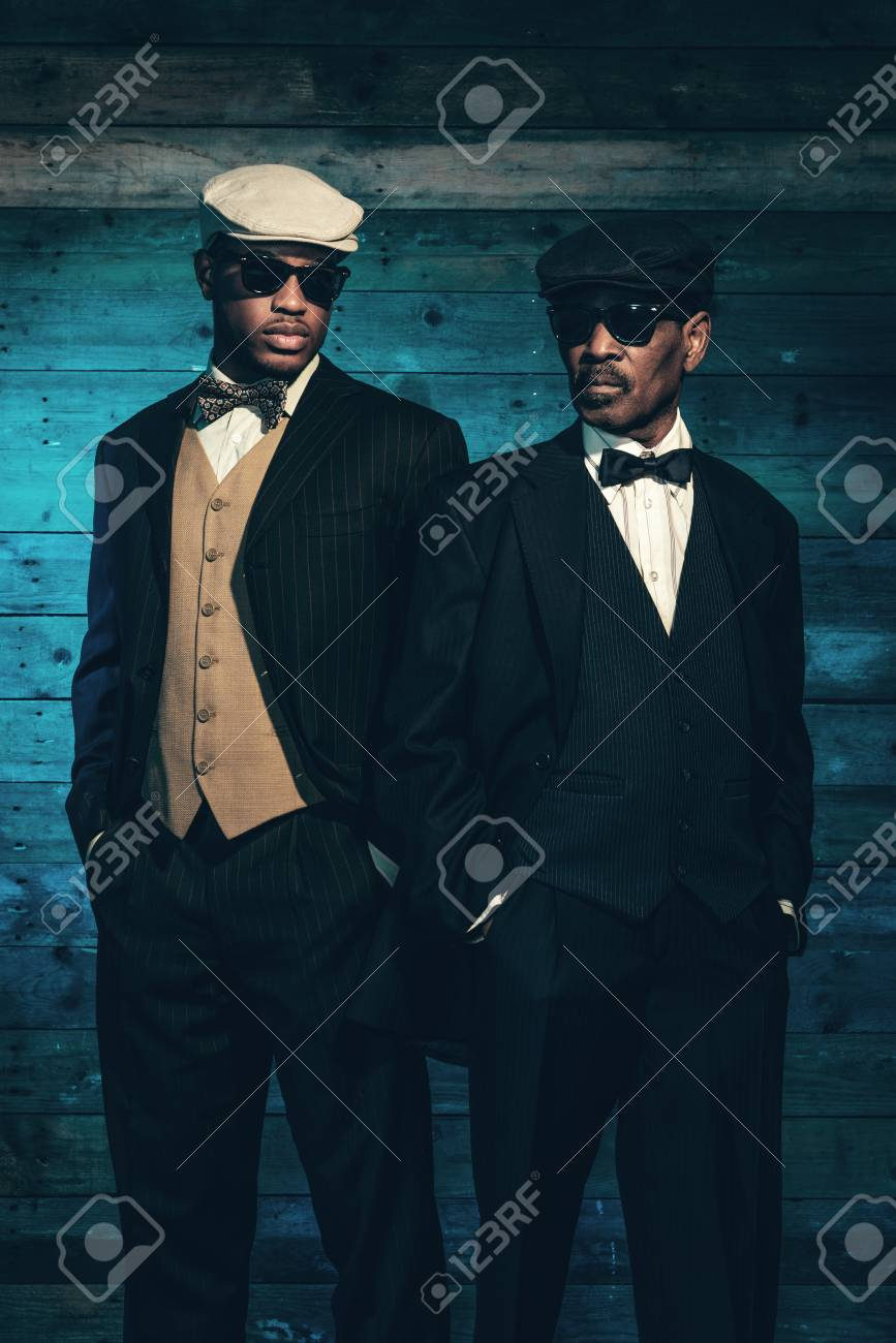 Stock Photo - Two vintage african american gangsters in front of old wooden  wall. Wearing black sunglasses with suit and cap. 5cc5318b9db9