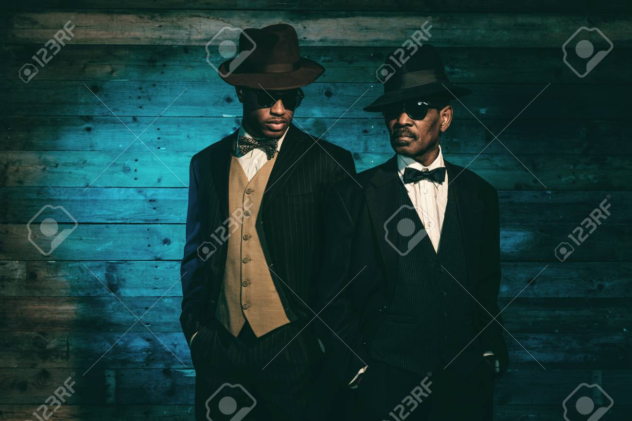 Stock Photo - Two vintage african american gangsters in front of old wooden  wall. Wearing black sunglasses with suit and hat. da7301cceaf2