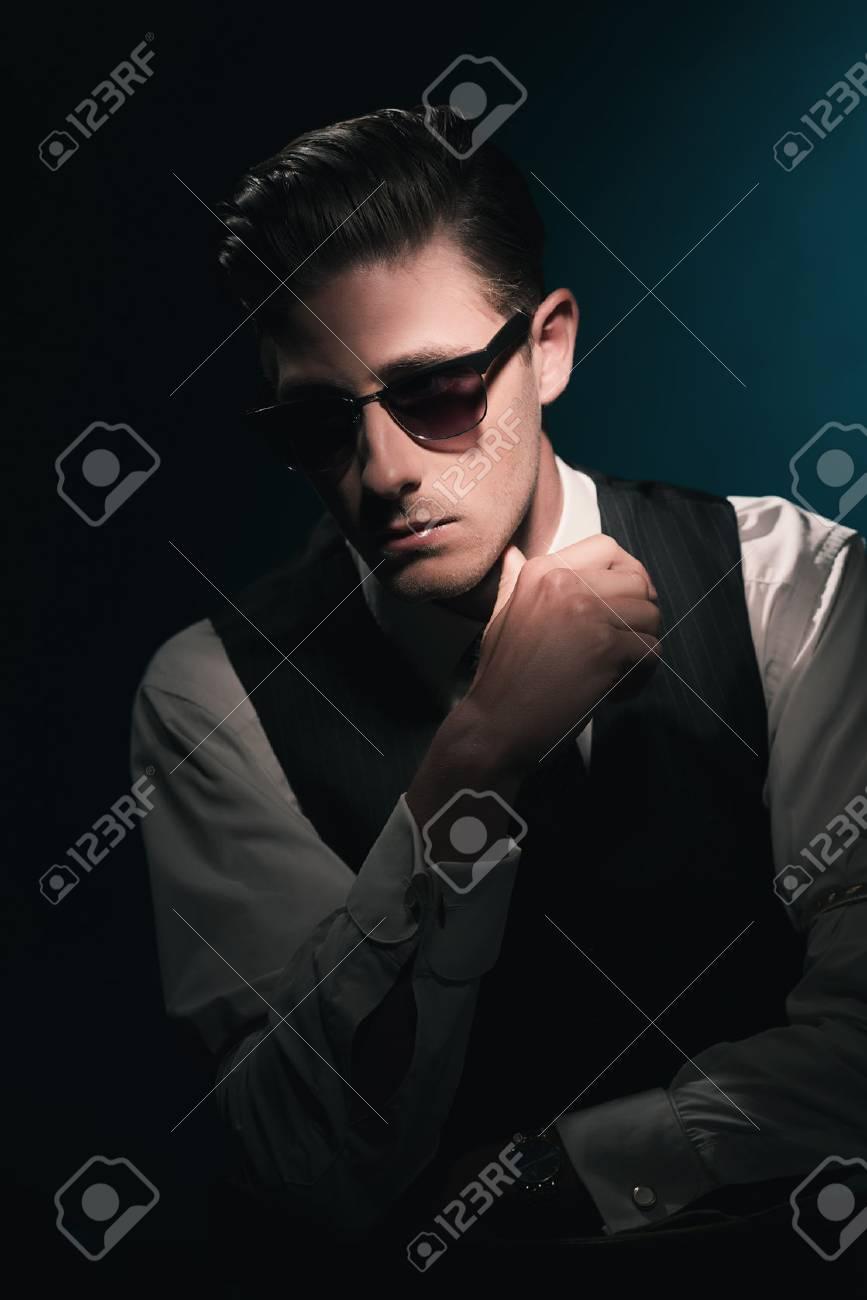 Hombre Clásico De La Manera Elegante Con Gafas De Sol En El Chaleco Y La Corbata El Cabello Graso Peinado Hacia Atrás Contra El Fondo Azul Oscuro