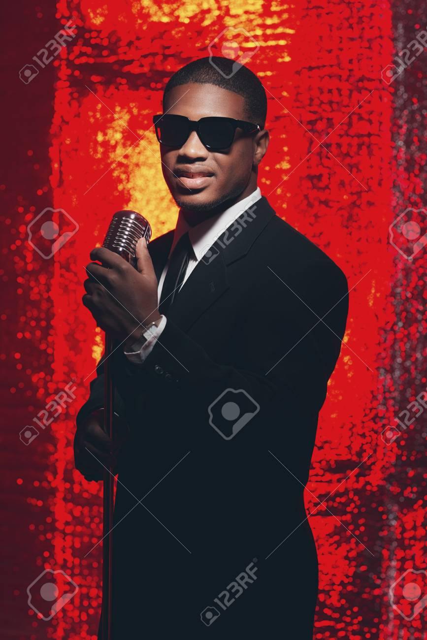 large choix de designs rechercher le meilleur styles classiques Sourire rétro 50s mâle africain chanteur américain avec des lunettes de  soleil en costume noir et cravate. fond réfléchissant rouge.