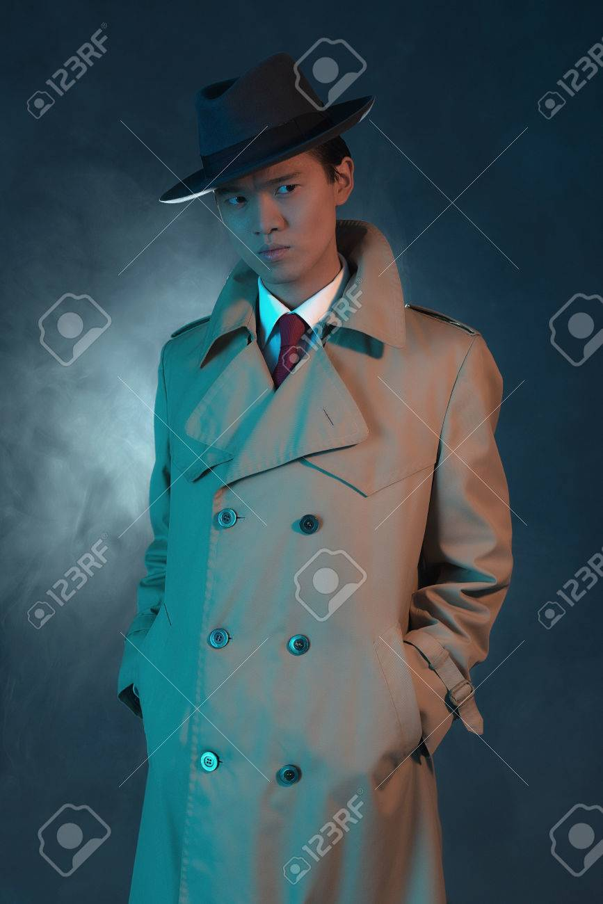 mysterious retro 1940 asian gangster fashion man in raincoat stock
