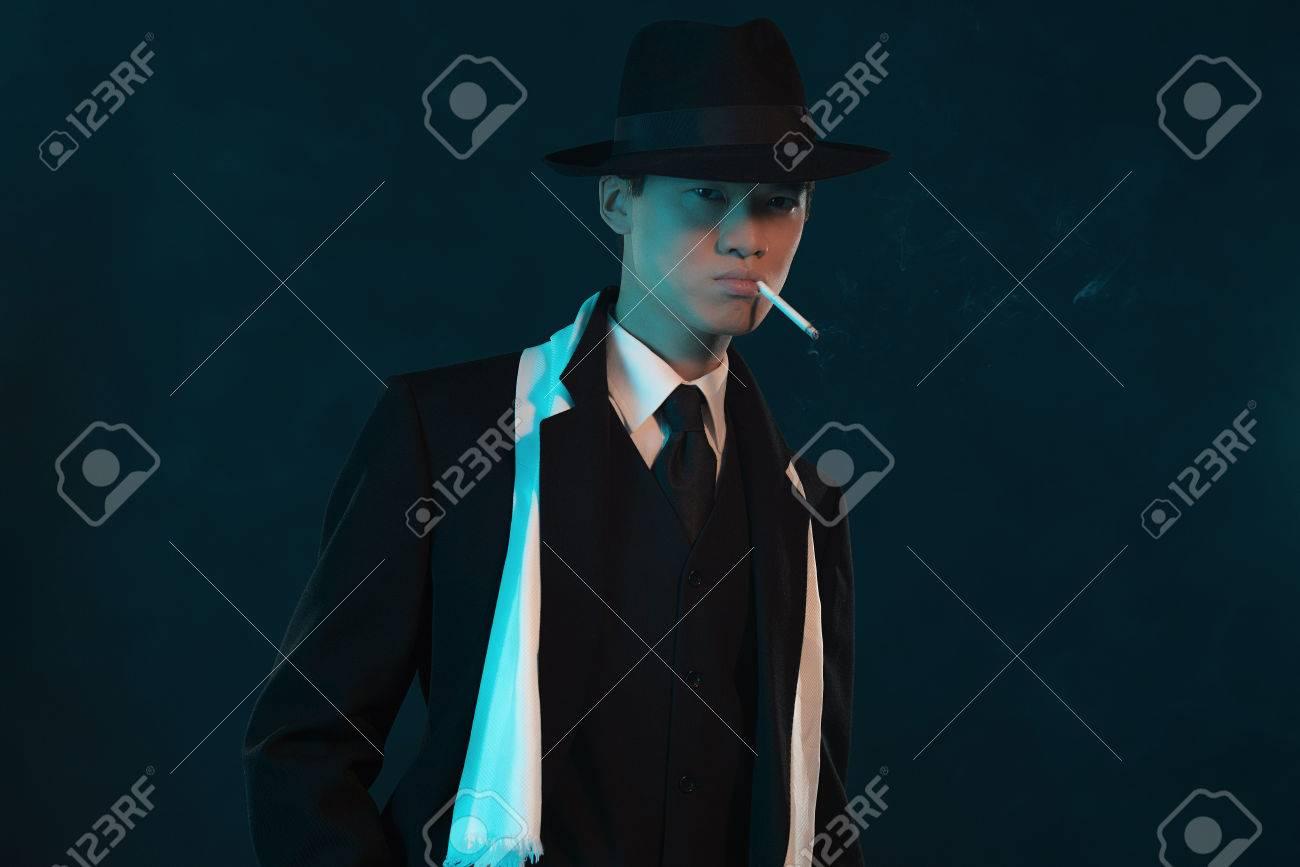 retro 1940 asian gangster fashion man smoking cigarette stock