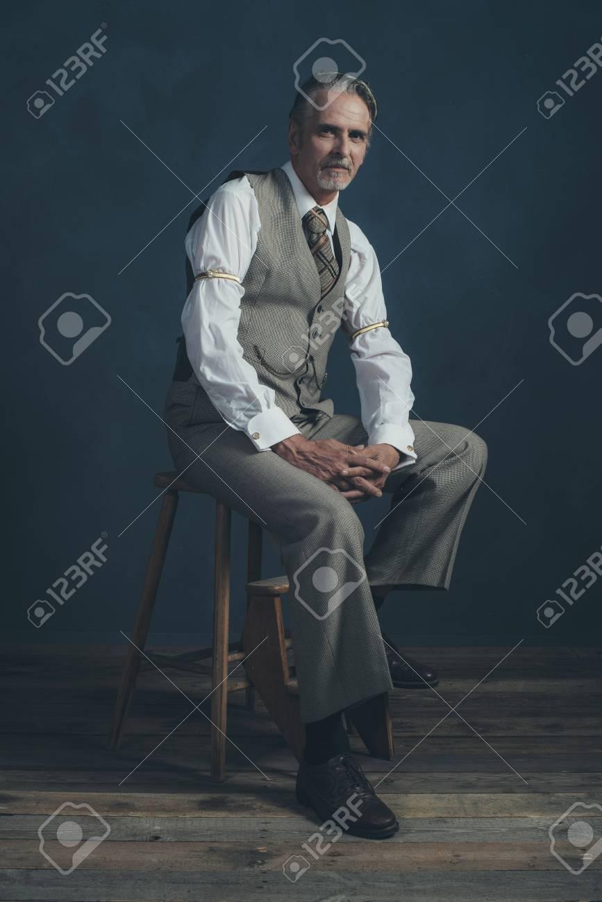 Homme de mode rétro années 1920 confiant assis sur une chaise en bois dans  une pièce vide.