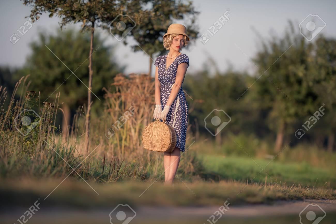 jahrgang 1930 sommer mode frau mit blauen kleid und strohhut mit handtasche  auf der landstraße stehen.