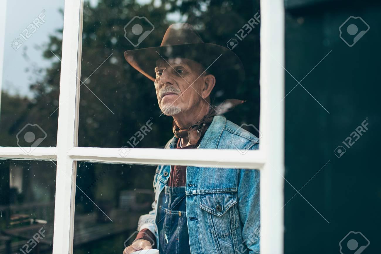 Agricoltore con barba e cappello tenendo la tazza di caffè guardando fuori  la finestra della vecchia 657917745820