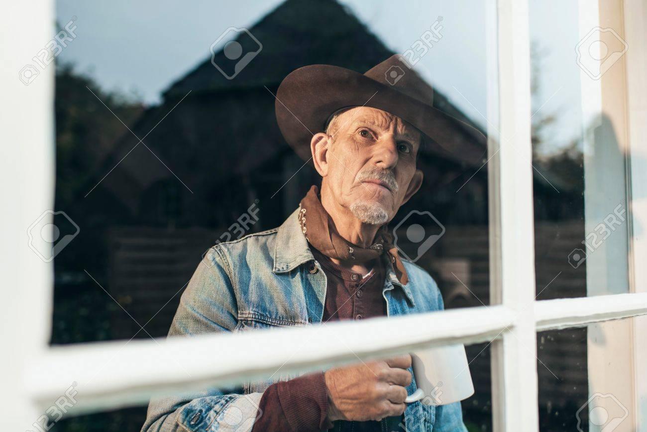 Archivio Fotografico - L uomo con la barba grigia e cappello tenendo la  tazza di caffè guardando fuori dalla finestra della vecchia fattoria. b09ae691b4d6