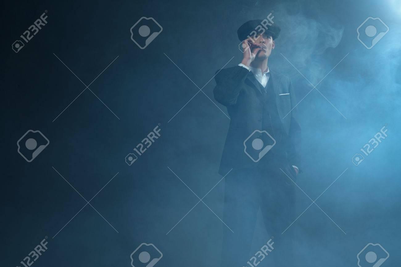 gran ajuste niño vendible Gángster inglés retro de los años 20 con traje y gorra plana de pie en la  habitación de humo. Fumar cigarrillo Estilo de anteojos pico.