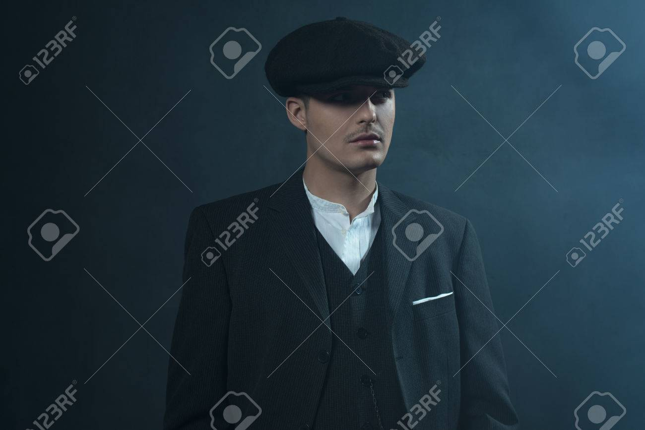 Retro 1920s english gangster wearing suit and flat cap standing in smoky  room. Peaky blinders abca04df633