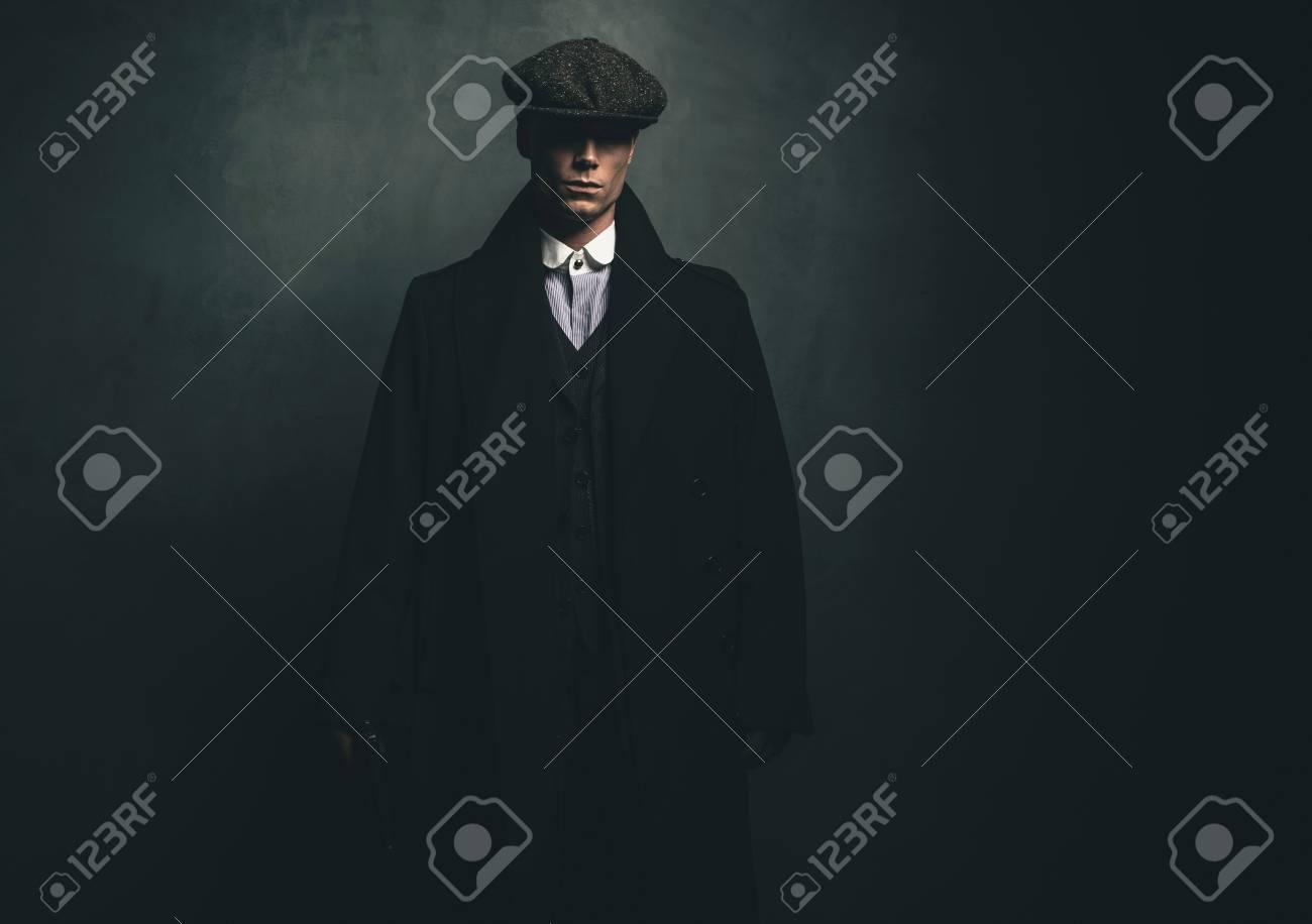 vendible oficial mejor calificado profesional Misterioso retro gángster inglés de 1920 con gorra plana y abrigo negro.