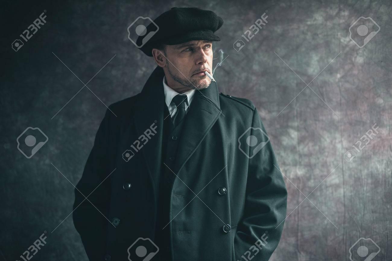venta caliente online estilo novedoso Zapatillas 2018 Cigarrillo que fuma del gángster inglés retro de los años 20. Llevando  abrigo negro y gorra plana.