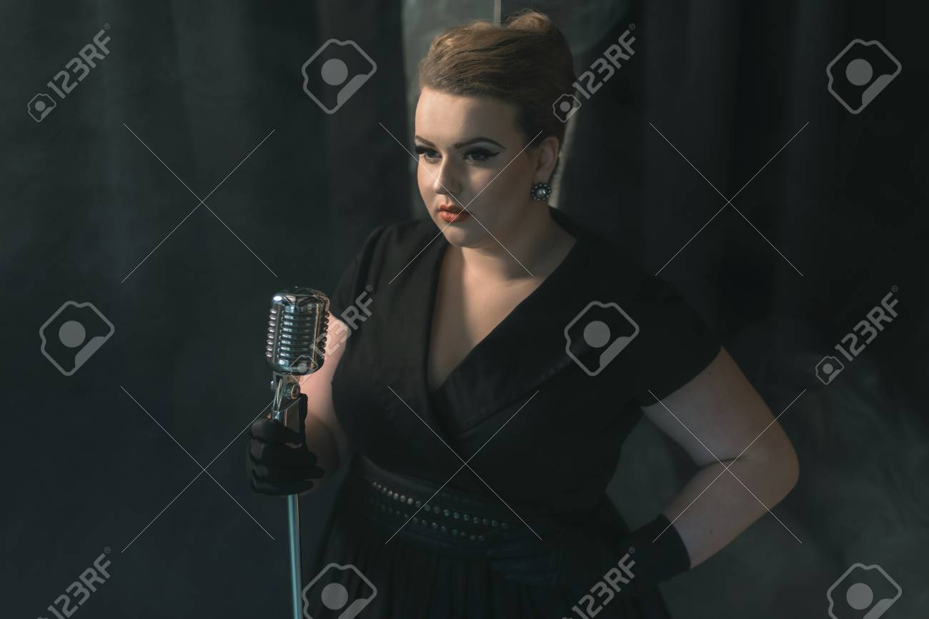 Retro 1950s female singer on smoky stage with black curtain
