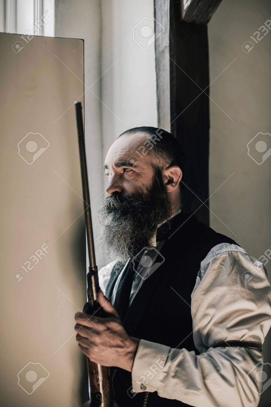Man with long beard holding rifle looking through gap of light of open door. Stock & Man With Long Beard Holding Rifle Looking Through Gap Of Light ...