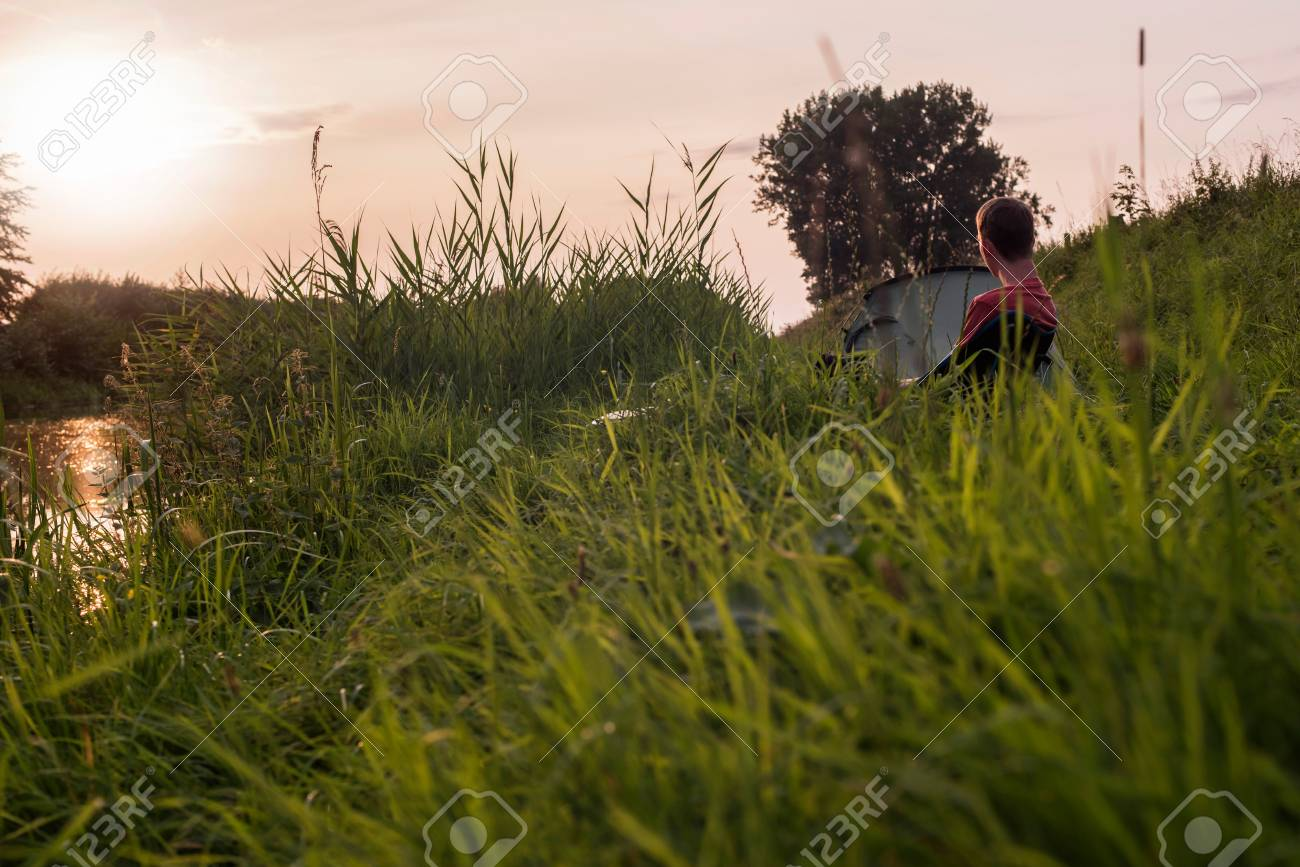 Trekking Man Sitting On Chair At Campsite In Tall Grass