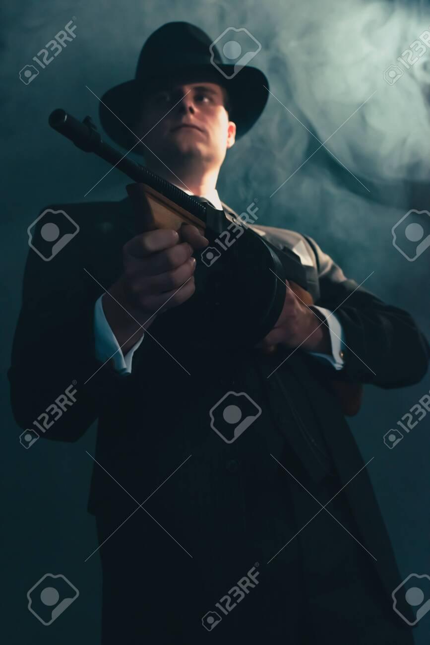 Retro gangster in hat in misty night shoots with machine gun. - 130454865