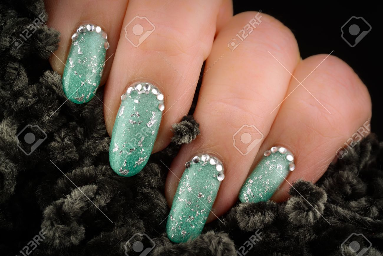 Green Nails With Glitter And Rhinestones On A Dark Background Stock ...