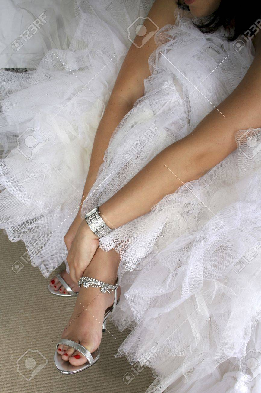 74ec0f859515 Bride in white wedding dress putting on silver shoes Stock Photo - 8600803