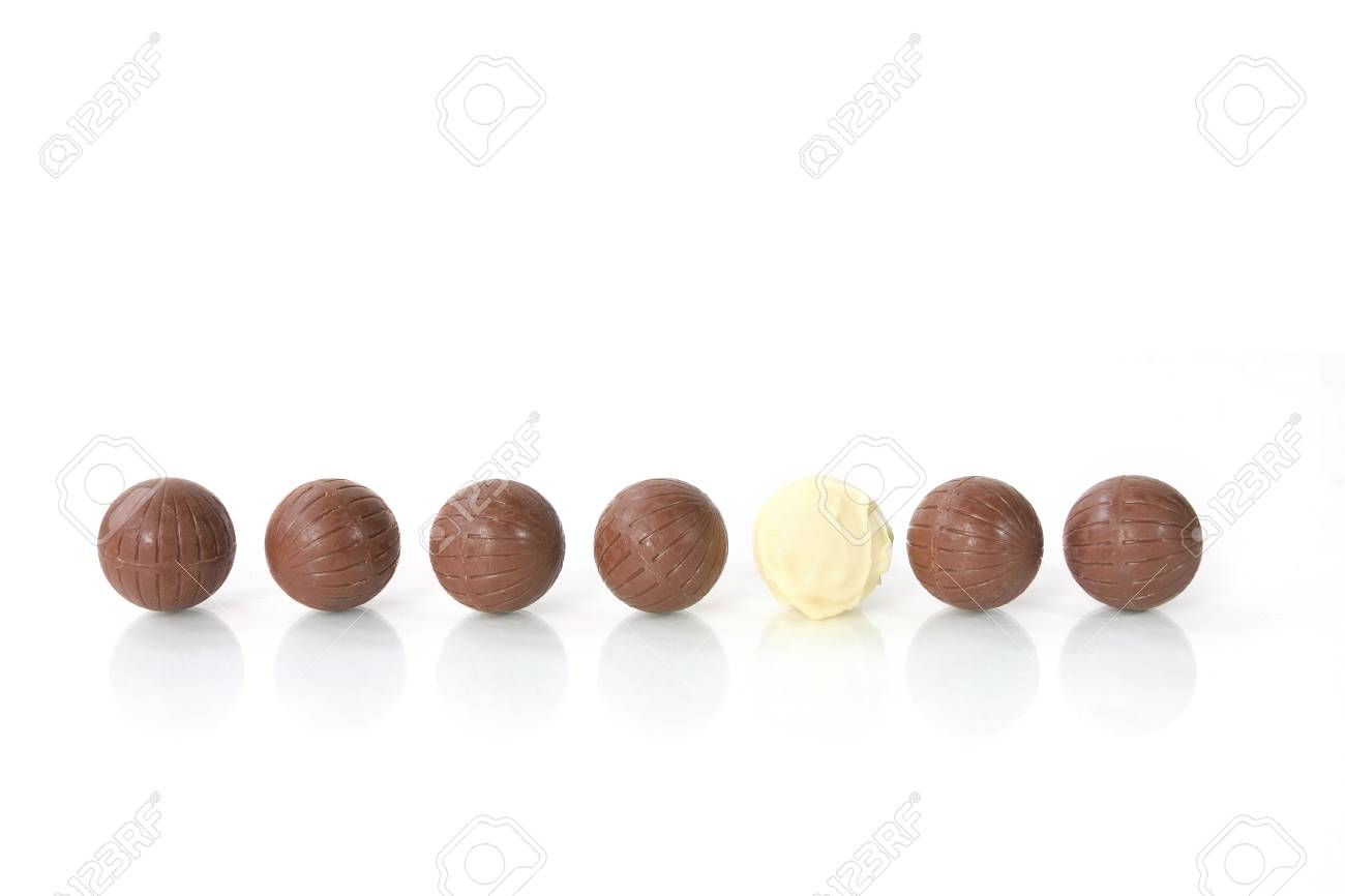 To be different - a white chocolate among a row of brown ones Stock Photo - 24532448