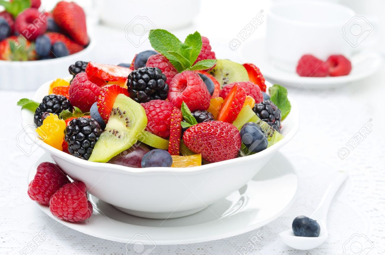 salad of fresh fruit and berries in a white bowl, berries and a cup of tea in the background, horizontal closeup - 19579497