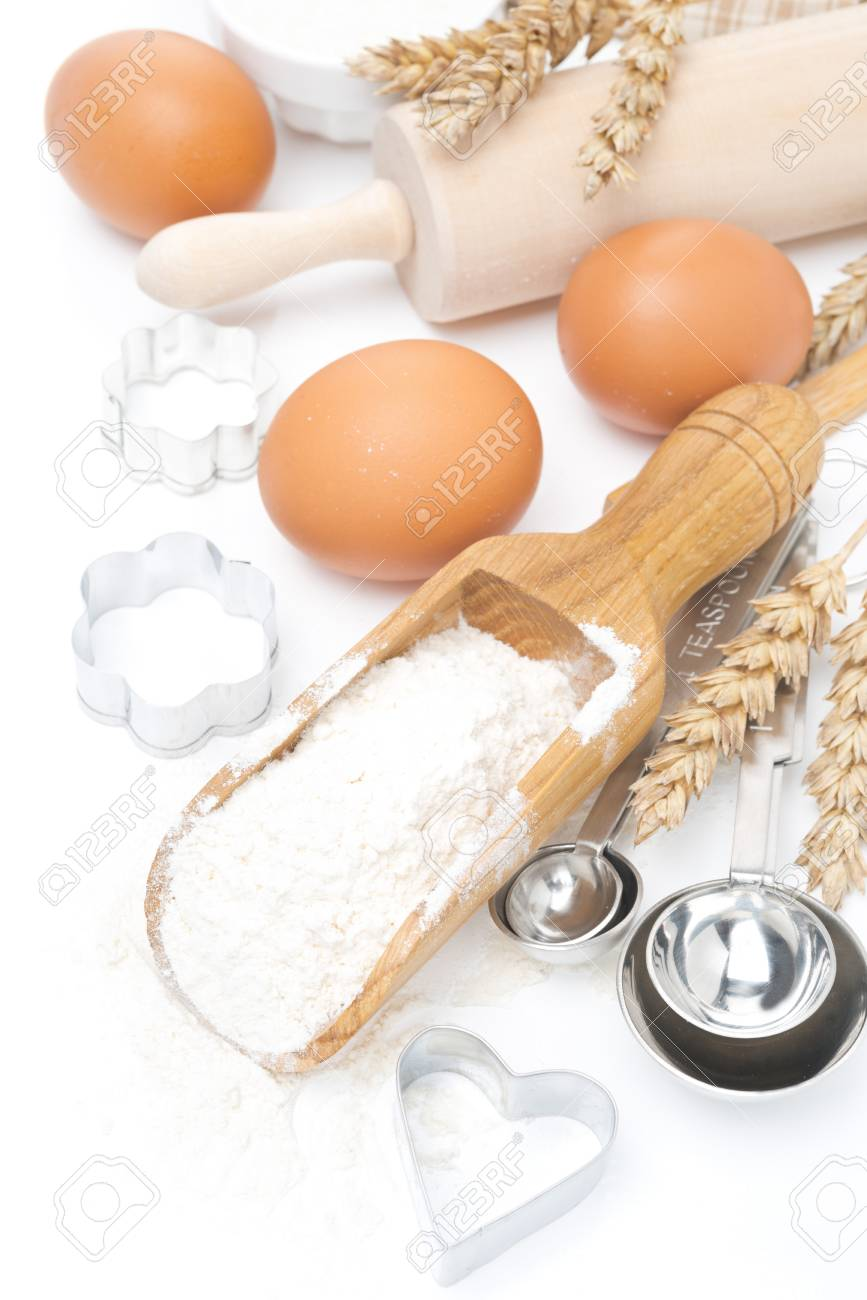 scoop with wheat flour, rolling pin, eggs and cookie cutters isolated on white Stock Photo - 22315845